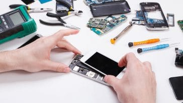 Repairman Disassembling Phone For Inspecting